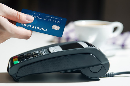 Woman hand using payment terminal in restaurant Stockfoto