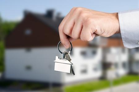chrome man: Man hand holding keys with to new house. Home shape chrome pendant