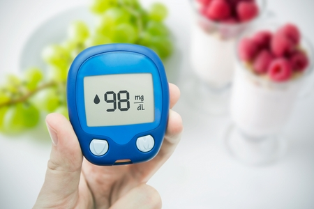 blood sugar: Hand holding meter. Diabetes doing glucose level test. Fruits in background Stock Photo