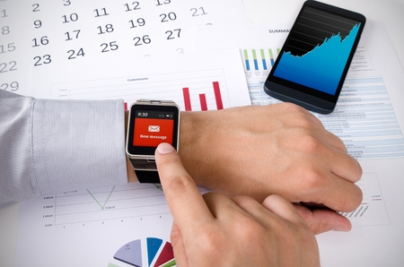 new message: Man working with smart watch in office. New message received notification on screen