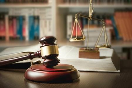 abogado: Juzgue el mazo y la escala en la corte. Biblioteca con gran cantidad de libros de fondo Foto de archivo