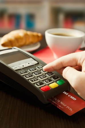 Man making payment with terminal for sale in cafeteria or restaurant