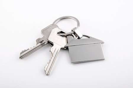 Keys and house chrome pendant with home shape isolated on white background