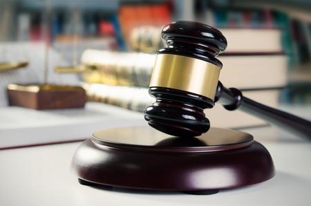 De hamer en de schaal in de rechtbank. Bibliotheek met veel boeken in de achtergrond