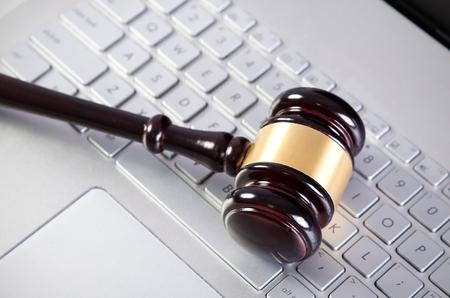 ラップトップ コンピューターの白いキーボードに木製裁判官ハンマー 写真素材