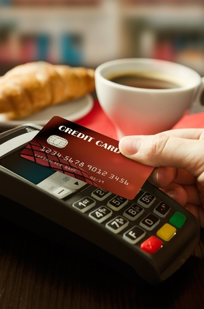 Man using payment terminal with NFC contactless technology in cafeteria Banque d'images