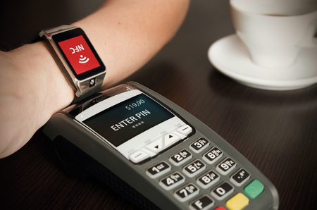 payments: Man making payment through smartwatch via NFC contactless technology Stock Photo