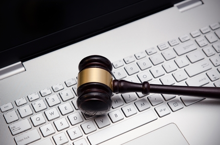 Houten rechter hamer op een laptop computer wit toetsenbord Stockfoto