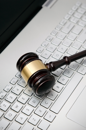 information technology law: Wooden judge hammer on laptop computer white keyboard