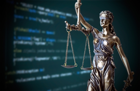 Justice statue with code on screen in background. Internet crime concept Stockfoto
