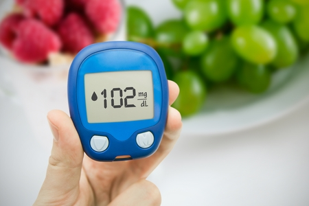 poking: Hand holding meter. Diabetes doing glucose level test. Fruits in background Stock Photo