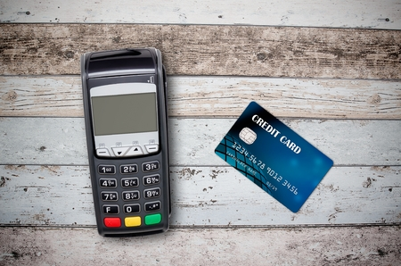 Payment terminal and credit card on wooden background top view