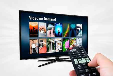 tv screen: Video on demand VOD service on smart TV. Remote control in hand. Stock Photo