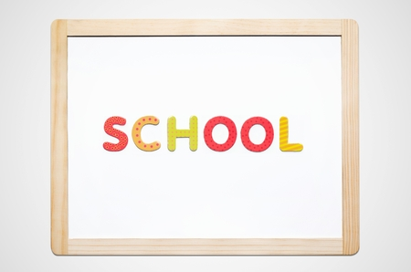white board: Hand put the word School on magnetic board. Colorful alphabet kit Stock Photo
