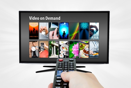 vod: Video on demand VOD service on smart TV. Remote control in hand. Stock Photo