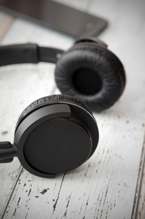 head phones: Wireless modern head phones and smart phone on wooden background