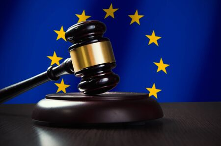 legality: Wooden gavel with European Union flag in background. Justice and law symbol