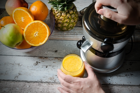 blend: Man preparing fresh orange juice. Fruits in background on wooden desk Stock Photo
