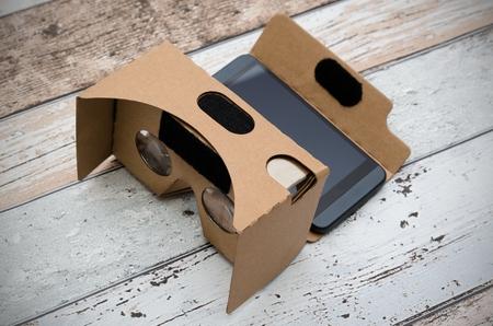 carton: gafas de realidad virtual de cartón. Una forma sencilla de ver películas en 3D. Disparar sobre fondo de madera.