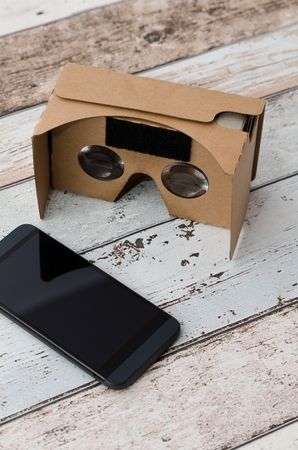 easy way: Virtual reality cardboard glasses. Easy way to watch movies in 3D. Shoot on wooden background. Stock Photo