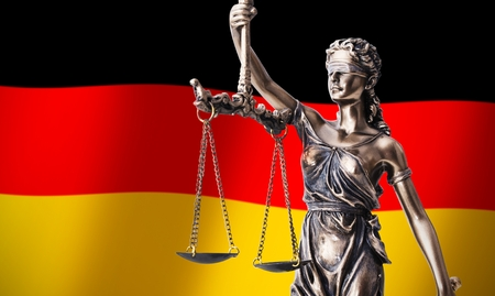government regulations: Themis with scale, symbol of justice on German flag background composition Stock Photo