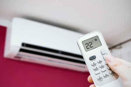 Air conditioner split on the wall. Hand holding remote control Standard-Bild