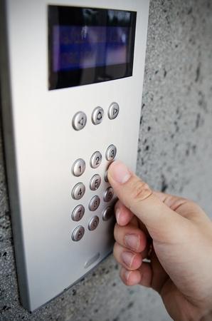 talc: Close up of finger pressing button on intercom numpad Stock Photo
