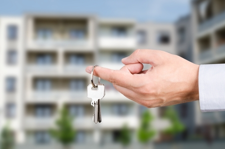 apartment building: Man hand holding on finger keys to new house. Stock Photo