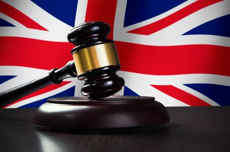 government regulations: Wooden gavel with United Kingdom flag in background. Justice and law symbol