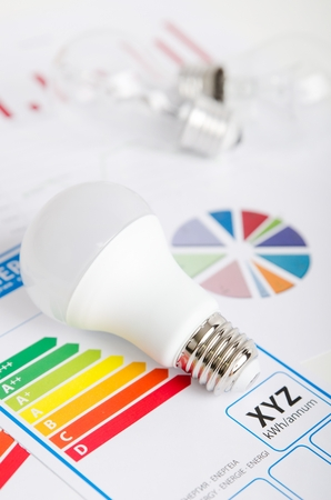 e27: LED light bulb on energy efficiency chart. Economic concept
