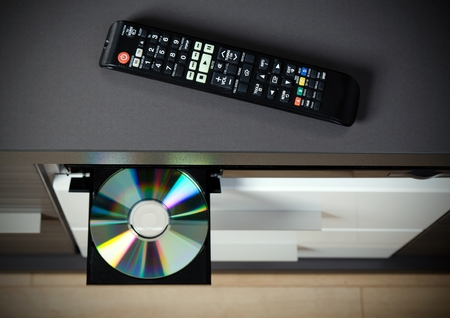 bluray: Remote control and Blu-ray or DVD player with inserted disc.