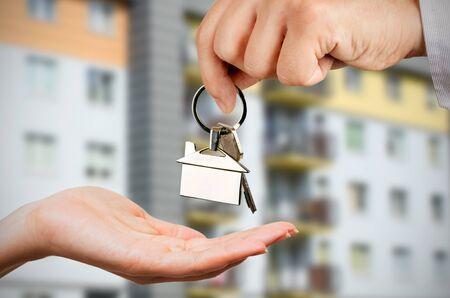 pedant: Man gives a woman the keys to a new home. Chrome pedant with house shape