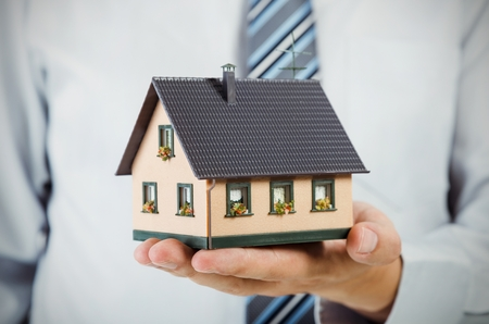 Realtor holding house miniature. Home budget and finance concept Stock Photo