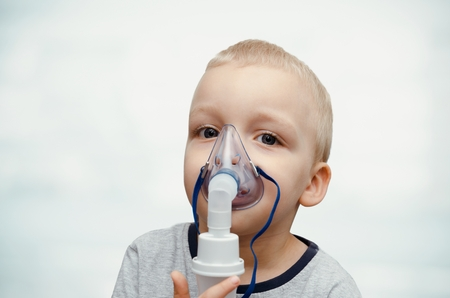 asthmatic: Child making inhalation with mask on his face. Asthma problems concept