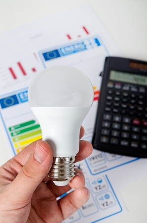e27: Hand holding LED bulb. Energy efficiency chart and calculator in background