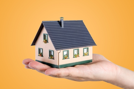 hand holding house: Hand holding house miniature. Home budget and finance concept