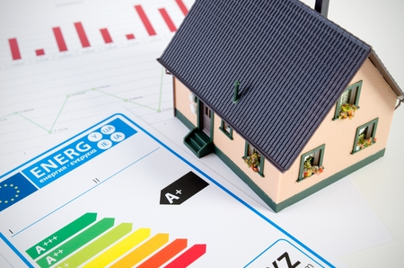 eficiencia: Concepto del rendimiento energético con el modelo y los documentos en el escritorio de casa Foto de archivo