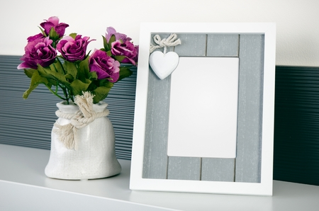 photo frame: Photo frame stands on a shelf next to the flowers. House decoration Stock Photo