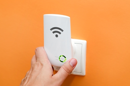 WiFi repeater in electrical socket on orange wall. Simply way to extend wireless network in home
