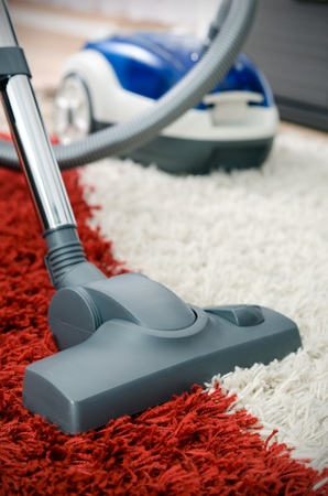 shaggy: Blue vacuum cleaner on shaggy carpet inside room close up Stock Photo