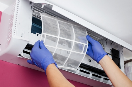 air: Air conditioner cleaning. Man in gloves checks the filter. Stock Photo