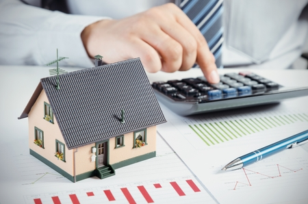 maintaining: Businessman calculate the cost of building and maintaining house. Home finance conception Stock Photo