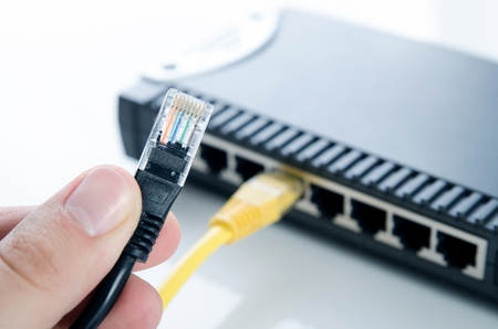 Network switch device and ethernet cables on white background Stock Photo