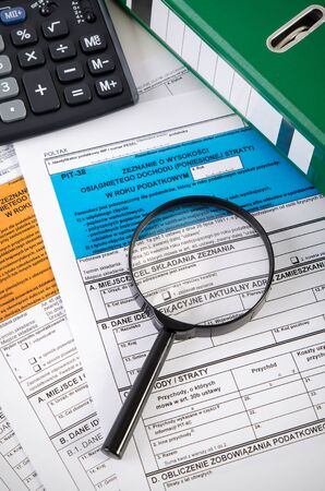folder with documents: Close up of Polish income tax forms on desk. Accountant performs tax settlements Stock Photo