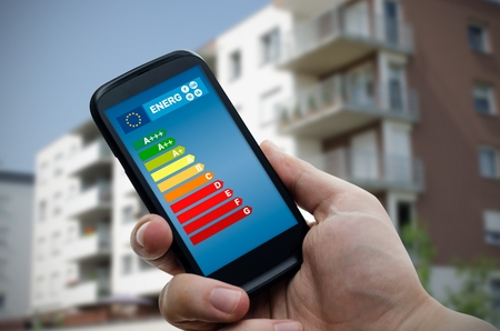 eficiencia: Man holding smartphone with energy efficiency chart. Savings in home concept