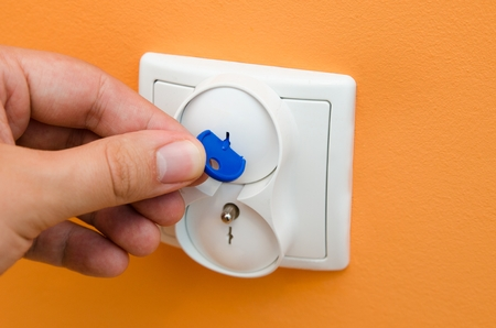 safe house: Man puts electrical security plugs for baby and child safety Stock Photo