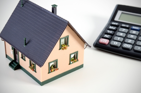 home finances: Home finances or saving for a house. House miniature and calculator