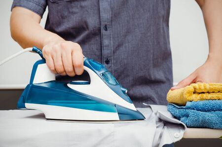 iron curtains: Man irons clothes on ironing board with steaming blue iron
