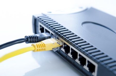 computer system: Network switch device and ethernet cables on white background Stock Photo