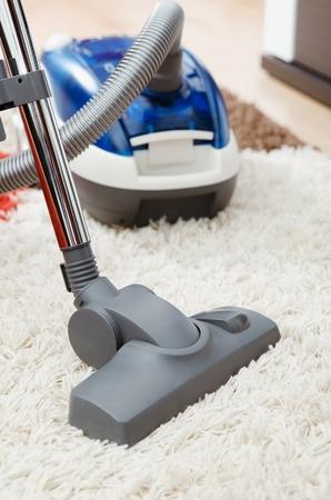 personal de limpieza: aspiradora azul en la alfombra lanuda dentro de la sala de cerca